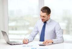Smiling businessman with laptop and documents Royalty Free Stock Image