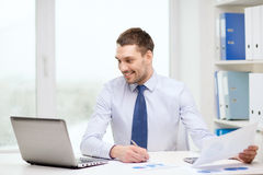 Smiling businessman with laptop and documents. Office, business, technology, finances and internet concept - smiling businessman with laptop computer and Royalty Free Stock Images