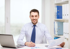 Smiling businessman with laptop and documents. Office, business, technology, finances and internet concept - smiling businessman with laptop computer and stock photography