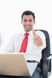 Smiling businessman with laptop gesturing thumbs up Royalty Free Stock Photography