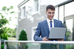 Smiling businessman with laptop. Smiling businessman with his laptop next to the office building Stock Photography