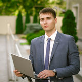 Smiling businessman with laptop. Smiling businessman with his laptop next to the office building Stock Photo