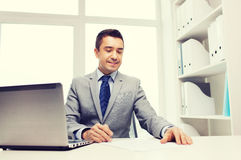 Smiling businessman with laptop and papers Stock Photos