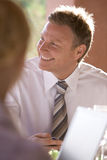 Smiling businessman with laptop on restaurant patio Royalty Free Stock Image