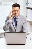 Smiling businessman with laptop and smartphone Stock Photography
