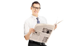 Smiling businessman leaning against wall and holding a newspaper Stock Image