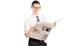 Smiling businessman leaning against wall and reading a newspaper Stock Photography