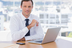 Smiling businessman leaning on his desk Stock Image