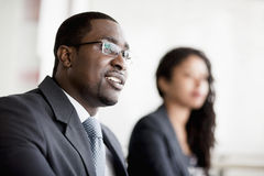 Smiling businessman listening at a business meeting Stock Images