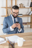 Smiling businessman listening music and using smartphone in earphones at workplace Royalty Free Stock Images