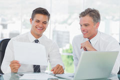 Smiling businessman listening to his intern while explaining doc Royalty Free Stock Images