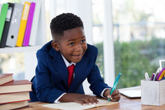 Smiling businessman looking away while writing on book Stock Images