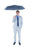 Smiling businessman looking at camera under umbrella Royalty Free Stock Photography