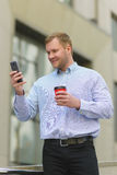 Smiling businessman looking on his cell phone outdoors Stock Images
