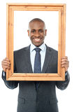 Smiling businessman looking through picture frame. Businessman standing behind wooden picture frame Stock Image