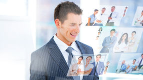 Smiling businessman looking at pictures Royalty Free Stock Images