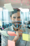 Smiling businessman looking through plans written on glass Royalty Free Stock Photos
