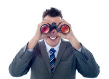 Smiling businessman looks through binoculars Royalty Free Stock Image