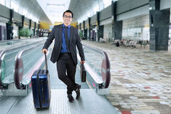 Smiling businessman with luggage in airport hall. Portrait of male entrepreneur in business suit smiling at the camera while carrying luggage and briefcase in Royalty Free Stock Photography