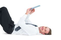 Smiling businessman lying and using tablet Royalty Free Stock Photos