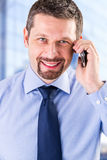 Smiling businessman making a phone call. Smiling businessman making a phone call in his office royalty free stock images