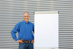 Smiling Businessman Making Presentation On Flipchart Royalty Free Stock Photos