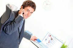 Smiling businessman making purchase by phone Stock Photo