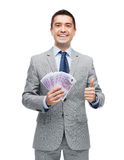 Smiling businessman with money showing thumbs up Royalty Free Stock Image