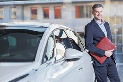 Smiling businessman with new automobile Royalty Free Stock Image