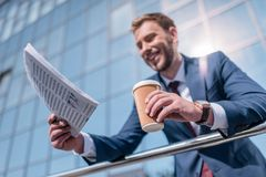 smiling businessman with newspaper and disposable cup of coffee standing Royalty Free Stock Photo