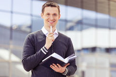 Smiling businessman with notepad and pen Stock Photo