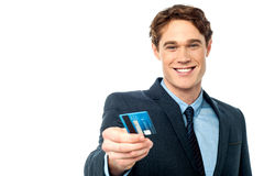 Smiling businessman offering his debit card to you. Smiling businessman handing over his debit card royalty free stock photos