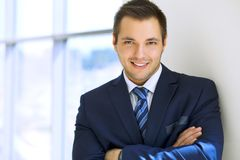 Smiling businessman  in office. Smiling businessman in office with arms crossed Stock Images