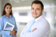 Smiling businessman  in office with colleagues in the background. Smiling businessman in office with colleagues in the background Royalty Free Stock Images