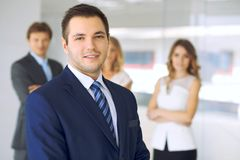 Smiling businessman in office with colleagues in the background stock image