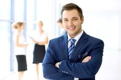 Smiling businessman in office with colleagues in the background royalty free stock image