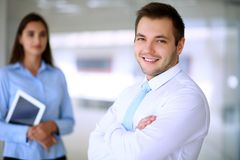 Smiling businessman in office with colleagues in the background stock photos
