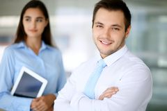 Smiling businessman in office with colleagues in the background stock photo