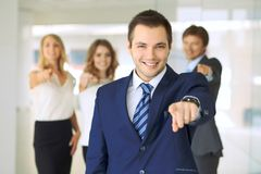 Smiling businessman in office with colleagues in the background. Pointing by finger into the camera royalty free stock photo
