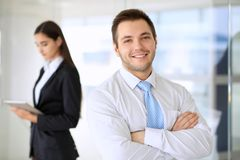 Smiling businessman  in office with colleagues in the background. Smiling businessman in office with colleagues in the background Royalty Free Stock Photos