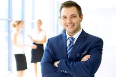 Smiling businessman in office with colleagues in the background.  stock photo