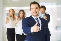 Smiling businessman in office with colleagues in the background. Thumbs up! stock photography