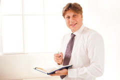 Smiling Businessman in office holding diary Royalty Free Stock Photography