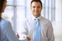 Smiling businessman in office is shaking hands with his partner.  Royalty Free Stock Photography