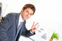 Smiling businessman in office showing victory Royalty Free Stock Photos