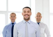 Smiling businessman in office with team on back Stock Photo