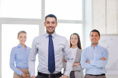 Smiling businessman in office with team on back Royalty Free Stock Photos