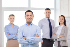 Smiling businessman in office with team on back Royalty Free Stock Images