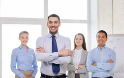 Smiling businessman in office with team on back Stock Photos