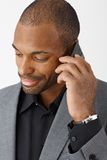 Smiling businessman on phone call. Smiling ethnic businessman concentrating on mobile phone call, closeup portrait Royalty Free Stock Images